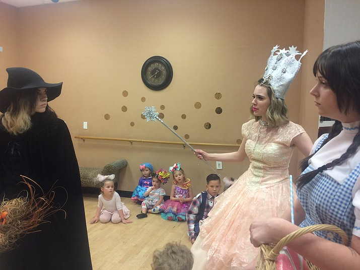 """Nicolette Stefanic as the Wicked Witch of the West glares at Dorothy Gale, played by Paige Phillips with McKenna Gall as the Glinda the Good Witch of the North and the Munchkins of Oz behind them during a dress rehearsal for One Stage Family Theatre's """"Wizard of Oz."""" (Jason Wheeler/Courier)"""