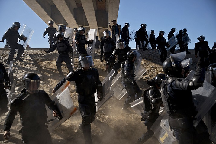 In this Nov. 25, 2018 file photo, Mexican police run as they try to keep migrants from getting past the Chaparral border crossing in Tijuana, Mexico, near San Ysidro, Calif. A San Diego TV station says the U.S. government ran an operation to screen journalists, activists and others while investigating last year's migrant caravan from Mexico. KNSD-TV says documents leaked by a Homeland Security source show a January database listing at least 10 journalists, seven of them U.S. citizens, as warranting secondary screening at U.S. points of entry. (Ramon Espinosa/AP, file)
