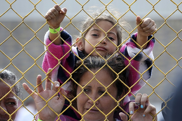 "Six-year-old Daniela Fernanda Portillo Burgos sits on the shoulders of her mother, Iris Jamilet, 39, as they look out through the fence of a immigrant shelter in Piedras Negras, Mexico, Tuesday, Feb. 5, 2019. A caravan of about 1,600 Central American migrants camped Tuesday in the Mexican border city of Piedras Negras, just west of Eagle Pass, Texas. The governor of the northern state of Coahuila described the migrants as ""asylum seekers,"" suggesting all had express intentions of surrendering to U.S. authorities. (Jerry Lara/The San Antonio Express-News via AP)"