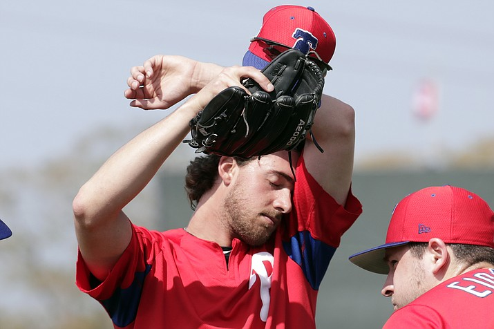 In this Feb. 19, 2019, file photo, Philadelphia Phillies starting pitcher Aaron Nola wipes his face at the Phillies spring training baseball facility, in Clearwater, Fla. It may look like a few weeks of relaxed fun in the sun, but make no mistake: Spring training can be a grind. Pitchers need to build their arms up slowly, and position players face their own challenges. At this time of year, Florida and Arizona are obviously better for baseball than many other American climates, but the warm, sunny weather does have a few drawbacks. (Lynne Sladky/AP, file)