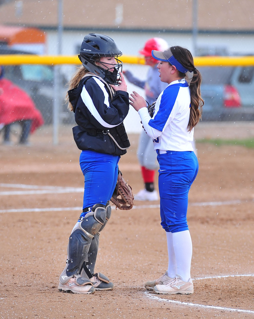Prescott's Danner Cozens and Makayla Reyes talk on the mound after giving up a homer as the Badgers host Seton Catholic on a blustery day Friday, March 8, 2019. Les Stukenberg/Courier)