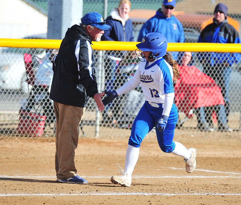 Prescott's Makayla Reyes gets congratulated by head coach Randall Bryan after hitting a solo home run in the first inning as the Badgers host Seton Catholic on a blustery day Friday, March 8, 2019. Les Stukenberg/Courier)