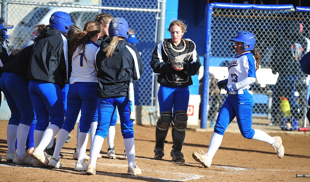 Prescott's Makayla Reyes gets congratulated by her teammates after hitting a solo home run in the first inning as the Badgers host Seton Catholic on a blustery day Friday, March 8, 2019. Les Stukenberg/Courier)