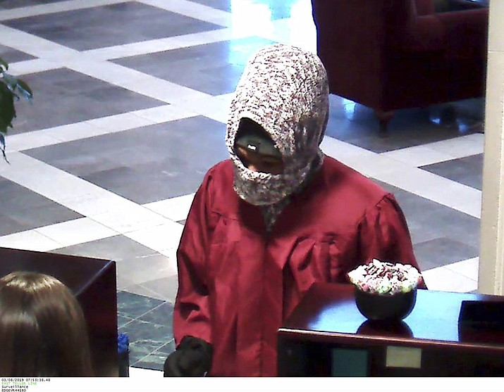 """This Friday March 8, 2019 image from surveillance video released by the Fargo Police Department shows a bank robbery by a man who was wearing a graduation robe in Fargo, N.D. Police say the male suspect walked into Alerus Financial about 8 a.m. Friday and produced a note that said """"give me money or I'll shoot."""" Authorities say the man did not show a weapon. He was wearing a maroon or red graduation gown and fled on foot with an undetermined amount of cash. (Fargo Police Department via AP)"""