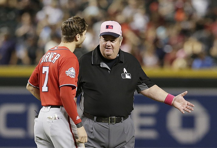 MLB umpire Joe West, right, talks with a player during a game between the Arizona Diamondbacks and the Washington Nationals in Phoenix on May 13, 2018. West, who has umpired more than 5,000 big league games, said the 2016 TrackMan computer system test was far from perfect. (Rick Scuteri/AP, File)
