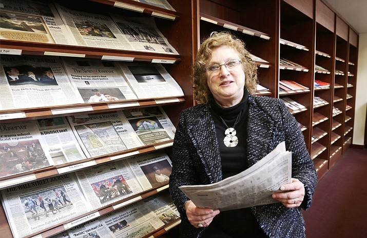 Penelope Muse Abernathy, a University of North Carolina professor, stands with the daily newspaper selection in the Park Library at the School of Journalism in Chapel Hill, N.C., on Thursday, March 7, 2019. (Gerry Broome/AP)
