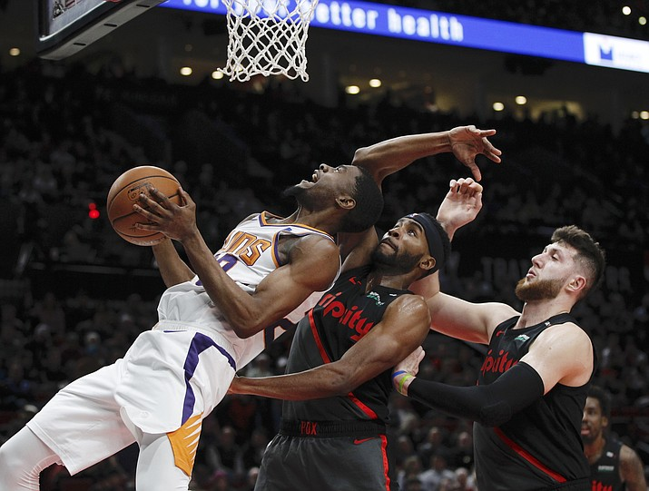 Phoenix Suns forward Josh Jackson, left, prepares to shoot as Portland Trail Blazers forward Maurice Harkless, center, and center Jusuf Nurkic, right, defend during the first half in Portland, Ore., Saturday, March 9, 2019. (Steve Dipaola/AP)