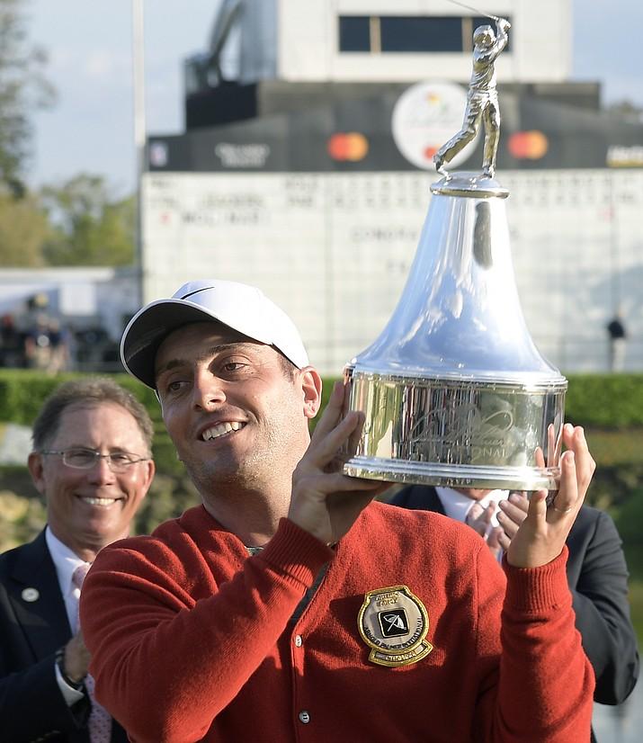 Francesco Molinari lifts the championship trophy after winning the Arnold Palmer Invitational golf tournament Sunday, March 10, 2019, in Orlando, Fla. (Phelan M. Ebenhack/AP)