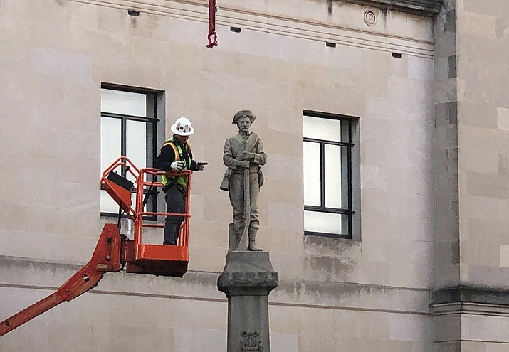 A workman prepares a Confederate staute for removal, Tuesday, March 12, 2019, in Winston-Salem, N.C. Crews began removing the Confederate statue Sunday from the grounds of an old courthouse. North Carolina has been at the forefront of the debate over what to do with Confederate monuments as one of three southern states with the most statues, according to the Southern Poverty Law Center. (Tom Foreman Jr./AP)