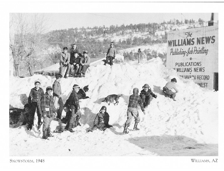 Children play in a large pile of snow in the empty lot next to the Williams News building in 1948. (Photo/Williams News)