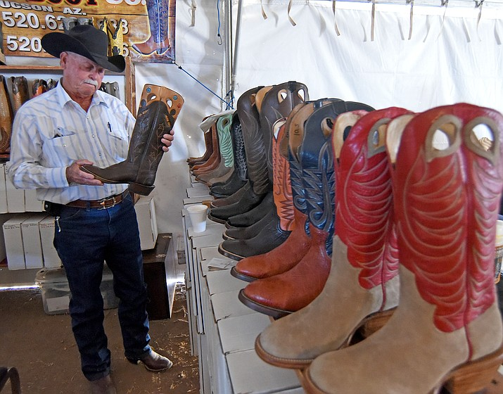 Dick Meyers of Peeples Valley hunts for a new pair of boots at the Ozuna Boot booth during the Cattleman's Trade Show Friday afternoon March 18, 2016, during the first day of the 25th Annual Cattleman's Weekend at the Prescott Livestock Auction in Chino Valley. (The Daily Courier file)