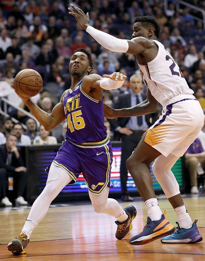 Utah Jazz guard Donovan Mitchell (45) drives as Phoenix Suns center Deandre Ayton defends during the first half of an NBA basketball game Wednesday, March 13, 2019, in Phoenix. (Matt York/AP)