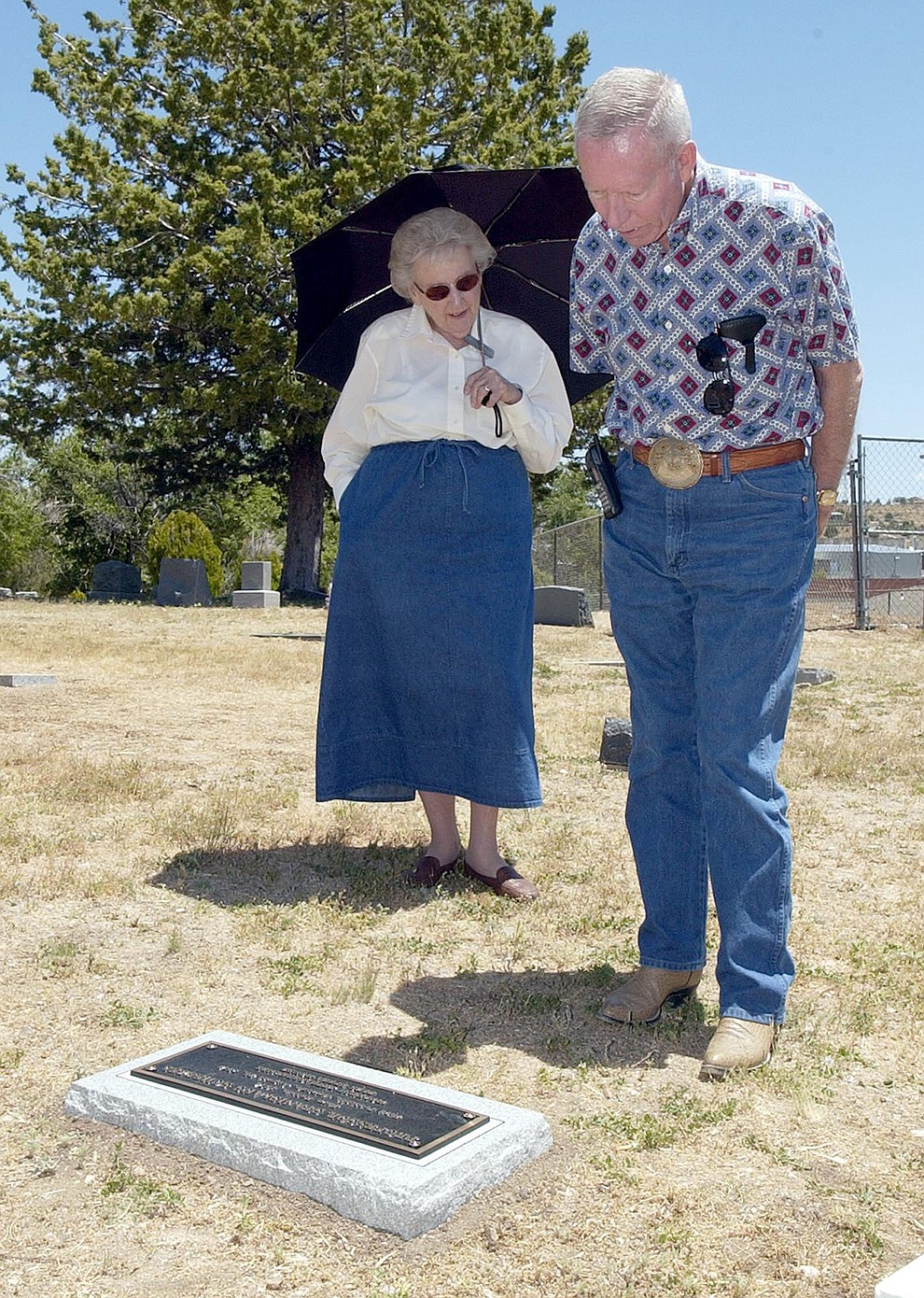Elisabeth Ruffner, left, and George Goodwin stand over the previously unmarked grave of Professor Stanislaus Scherzel in this file photo from June 2005 in Prescott.  Scherzel was a regular performer at the Elk's Theater in the early 1900's and took his own life in 1912. His grave in Mountain View Cemetery remained unmarked until the Yavapai Heritage Society and the Mountain View Cemetery donated the headstone in a Friday ceremony. (Courier file photo).