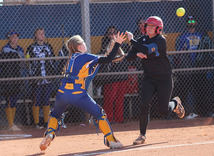 Kingman's Madi Bell, left, awaits a throw before tagging out Academy's Randa Short. The play proved crucial as the Lady Bulldogs won 2-1. (Photo by Beau Bearden/Daily Miner)