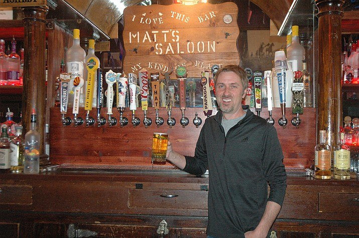 Matt Brassard, co-owner of Matt's Saloon, lifts a glass behind the bar. (Jason Wheeler/Courtesy)