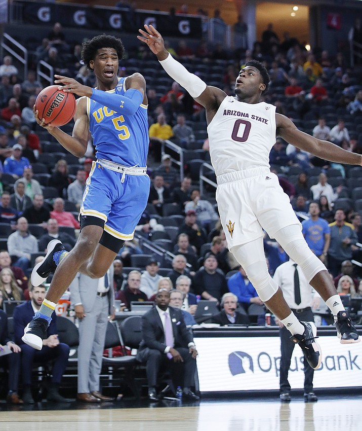 UCLA's Chris Smith, left, passes around Arizona State's Luguentz Dort during the first half of an NCAA college basketball game in the quarterfinals of the Pac-12 men's tournament Thursday, March 14, 2019, in Las Vegas. (John Locher/AP)