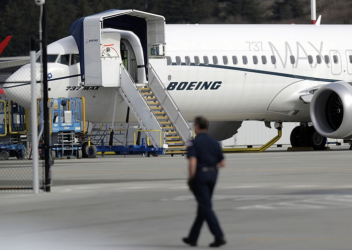 A worker walks next to a Boeing 737 MAX 8 airplane parked at Boeing Field, Thursday, March 14, 2019, in Seattle. The fatal crash Sunday of a 737 MAX 8 operated by Ethiopian Airlines was the second fatal flight for a Boeing 737 Max 8 in less than six months, and more than 40 countries, including the U.S., have now grounded the planes or refused to let them into their airspace. (Ted S. Warren/AP)
