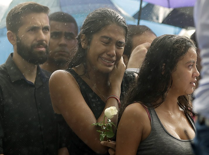 A woman stands weeping in the rain during the burial of 15-year-old student Kaio Lucas da Costa Limeira, a victim of a mass shooting at the Raul Brasil State School in Suzano, Brazil, Thursday, March 14, 2019. (Andre Penner/AP)