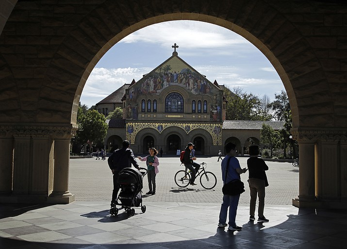 People walk near Memorial Church on the Stanford University campus Thursday, March 14, 2019, in Santa Clara, Calif. In the first lawsuit to come out of the college bribery scandal, several students are suing Yale, Georgetown, Stanford and other schools involved in the case, saying they and others were denied a fair shot at admission. (Ben Margot/AP)
