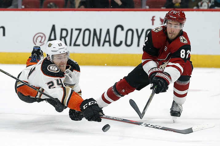 Anaheim Ducks center Carter Rowney (24) shoots in front of Arizona Coyotes defenseman Jordan Oesterle during the third period during an NHL hockey game Thursday, March 14, 2019, in Glendale, Ariz. Arizona defeated Anaheim 6-1. (Rick Scuteri/AP)