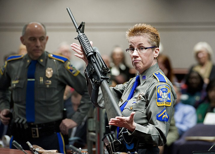 In this Jan. 28, 2013, file photo, firearms training unit Detective Barbara J. Mattson, of the Connecticut State Police, holds a Bushmaster AR-15 rifle, the same make and model used by Adam Lanza in the 2012 Sandy Hook School shooting, during a hearing at the Legislative Office Building in Hartford, Conn. A divided Connecticut Supreme Court ruled, Thursday, March 14, 2019, gun maker Remington can be sued over how it marketed the Bushmaster rifle used in the massacre. (AP Photo/Jessica Hill, File)