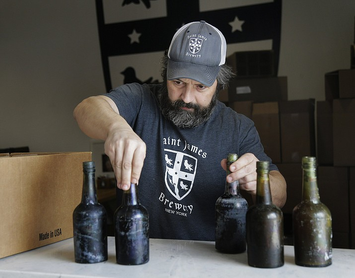 In this March 4, 2019, photo, Jamie Adams shows some intact beer bottles recovered from the shipwreck of the SS Oregon at his St. James Brewery in Holbrook, N.Y. Adams created an ale called Deep Ascent using the yeast from the bottles recovered from the Liverpool-to-New York luxury liner that sank off Fire Island in 1886. (AP Photo/Seth Wenig)