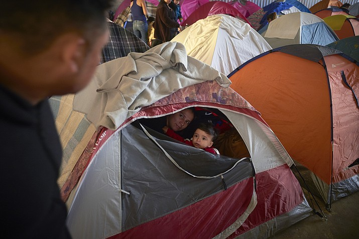In this March 5, 2019, image, Ruth Aracely Monroy, center, looks out of the family's tent alongside her 10-month-old son, Joshua, as her husband, Juan Carlos Perla, left, passes inside a shelter for migrants in Tijuana, Mexico. (AP Photo/Gregory Bull)