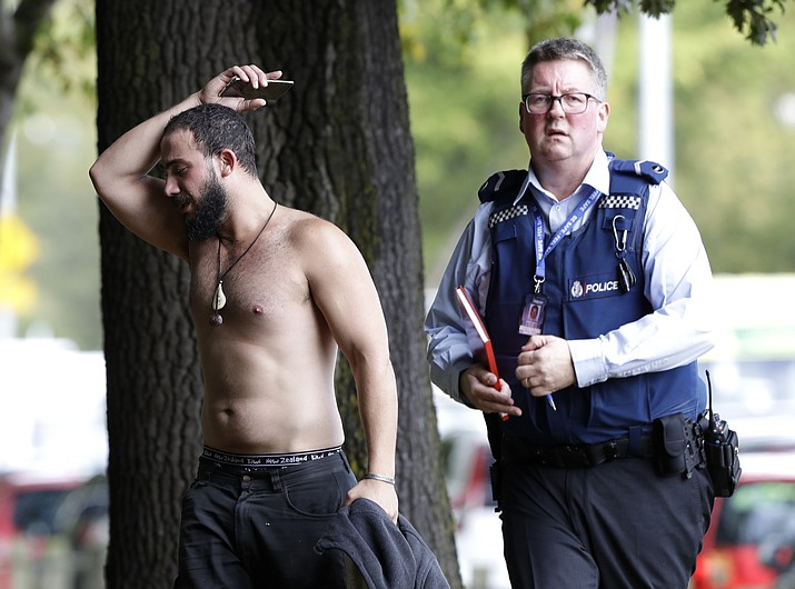 A police officer escorts a man away from a mosque in central Christchurch, New Zealand, Friday, March 15, 2019. Multiple people were killed in mass shootings at two mosques full of people attending Friday prayers, as New Zealand police warned people to stay indoors as they tried to determine if more than one gunman was involved. (Mark Baker/AP)