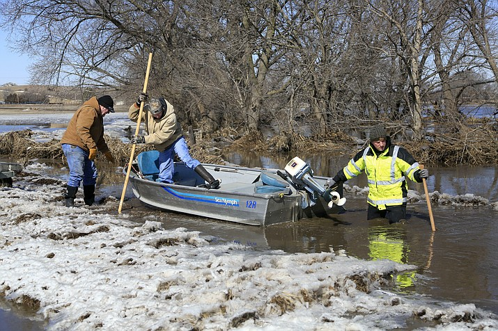 Tom Witke, left, his son Chad, center, and Nick Kenny, launch a boat into the swollen waters of the North Fork of the Elkhorn River, to check on Witke's flooded property, in Norfolk, Neb., Friday, March 15, 2019. (AP Photo/Nati Harnik)
