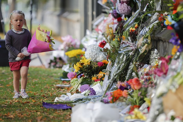 A girl walks to lay flowers on a wall at the Botanical Gardens in Christchurch, New Zealand, Sunday, March 17, 2019. New Zealand's stricken residents reached out to Muslims in their neighborhoods and around the country on Saturday, in a fierce determination to show kindness to a community in pain as a 28-year-old white supremacist stood silently before a judge, accused in mass shootings at two mosques that left dozens of people dead. (Vincent Thian/AP)