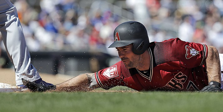 Arizona Diamondbacks' Matt Szczur dives safely back to first base on a pick-off attempt against the Chicago Cubs on Saturday, March 16, 2019, in Scottsdale. (Elaine Thompson/AP)