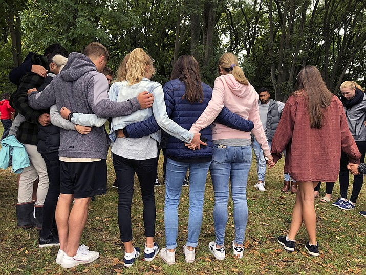 Mourners link arms in Hagley Park near the Al Noor mosque, one of the mosque shooting sites in Christchurch, New Zealand, Sunday, March 17, 2019. An attack on a New Zealand mosque took the lives of dozens of worshippers Friday and left dozens more wounded when a white supremacist opened fire and live-streamed the shootings. (Kristen Gelineau/AP)