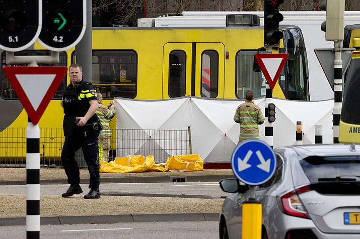Rescue workers install a screen on the spot where a body was covered with a white blanket following a shooting in Utrecht, Netherlands, Monday, March 18, 2019.  (AP Photo/Peter Dejong)