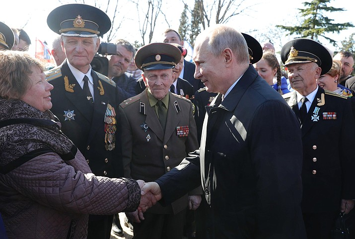 Russian President Vladimir Putin, right, meets with local residents and veterans at the historical memorial the Malakhov Kurgan (Malakoff redoubt) in Sevastopol, Crimea, Monday, March 18, 2019. Putin visited Crimea to mark the fifth anniversary of Russia's annexation of Crimea from Ukraine by visiting the Black Sea peninsula. (Mikhail Klimentyev, Sputnik, Kremlin Pool Photo via AP)