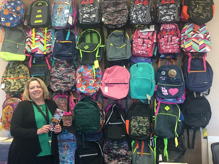Prescott Unified School District Homeless Program Liaison and Family Resource Center Coordinator Kelly Mattox stands in front of a wall of backpacks at the district's Family Resource Center. (Jason Wheeler/Courier)