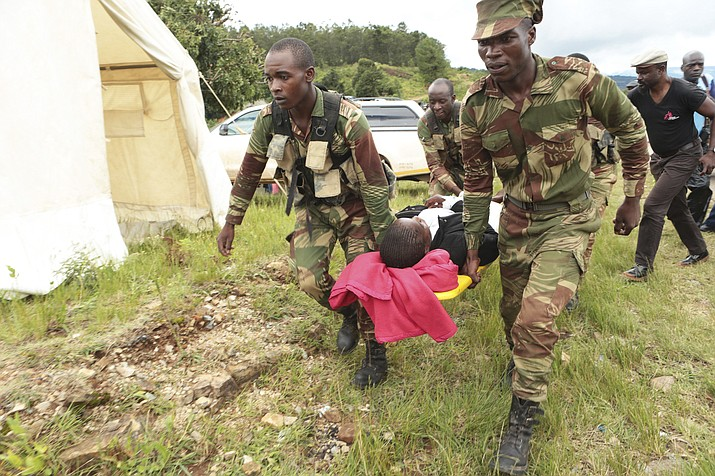 Soldiers carry injured survivors from a helicopter in Chimanimani about 600 kilometres southeast of Harare, Zimbabwe, on Tuesday, March, 19, 2019. According to the government, Cyclone Idai has killed more than 100 people in Chipinge and Chimanimani, and according to residents the figures could be higher because the hardest hit areas are still inaccessible. (Tsvangirayi Mukwazhi/AP)