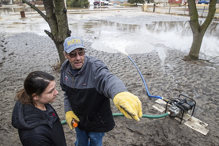 Brian Pemberton talks with Linzi Baker while trying to clear water from a home Tuesday, March 19, 2019, in Inglewood, Neb. Flooding is expected throughout the week in several states as high water levels flow down the Missouri River. Swollen rivers have already breached more than a dozen levees in Nebraska, Iowa and Missouri, according to the U.S. Army Corps of Engineers. (Brendan Sullivan/Omaha World-Herald via AP)