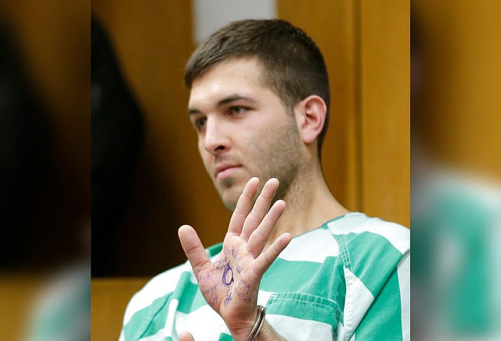 Anthony Comello displays writing on his hand that includes pro-Donald Trump slogans during his extradition hearing in Toms River, N.J., Monday, March 18, 2019. New York City police say a suspect is in custody in the shooting death of the reputed Gambino crime family boss. Chief of Detectives Dermot Shea says 24-year-old Comello was arrested Saturday, March 16, 2019, in the death of Francesco Cali on Wednesday in front of his Staten Island home. (AP Photo/Seth Wenig)