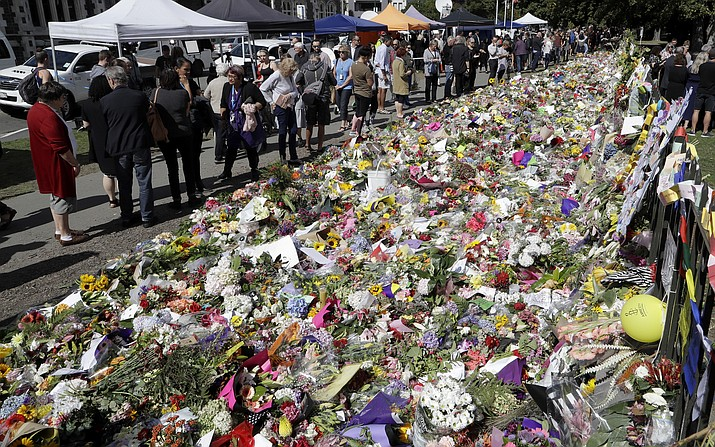 People view messages at a floral tribute at the Botanical Gardens in Christchurch, New Zealand, Tuesday, March 19, 2019. Christchurch was beginning to return to a semblance of normalcy Tuesday. Streets near the hospital that had been closed for four days reopened to traffic as relatives and friends of Friday's shooting victims continued to stream in from around the world. (Mark Baker/AP)
