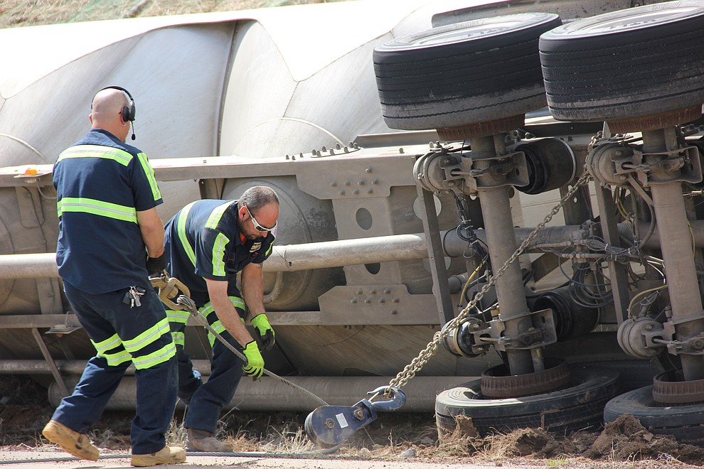 Jerry Hemme (left) and Fred Walker attach chains to the underbelly of a cement truck that tipped onto its side along Deep Well Ranch Road Tuesday, March 19, 2018 in Prescott. (Max Efrein/Courier)