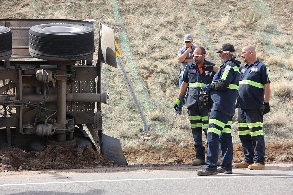 Fred Walker (left) Eddie Rackliff (center) and Jerry Hemme discuss how to get a tipped cement truck upright along Deep Well Ranch Road Tuesday, March 19, 2018 in Prescott. (Max Efrein/Courier)