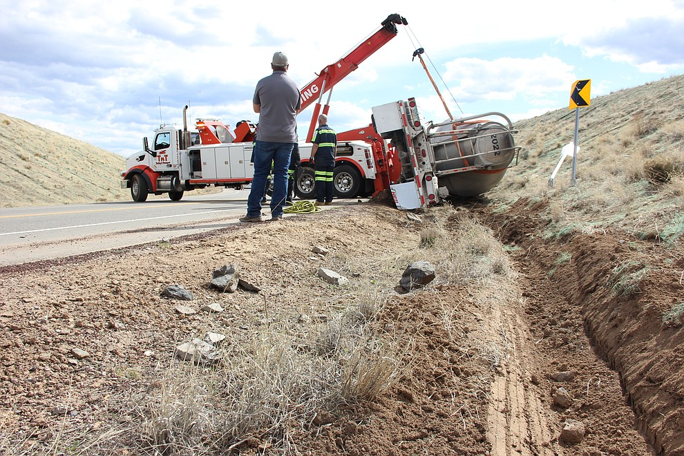 A towing crew works on righting a tipped cement truck along Deep Well Ranch Road in Prescott midday Tuesday, March 19. The truck had gone too fast around a sharp bend and careened off the road into a dirt bank. (Max Efrein/Courier)