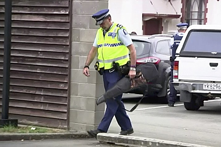 "In this image made from video taken March 19, 2019, a police officer carries a gun voluntarily surrendered by a member of the public into the Masterton police station in Masterton, New Zealand. Prime Minister Jacinda Ardern says New Zealand is immediately banning sales of ""military-style"" semi-automatic and automatic weapons like the weapons used in last Friday's attacks on two Christchurch mosques. (TVNZ via AP)"