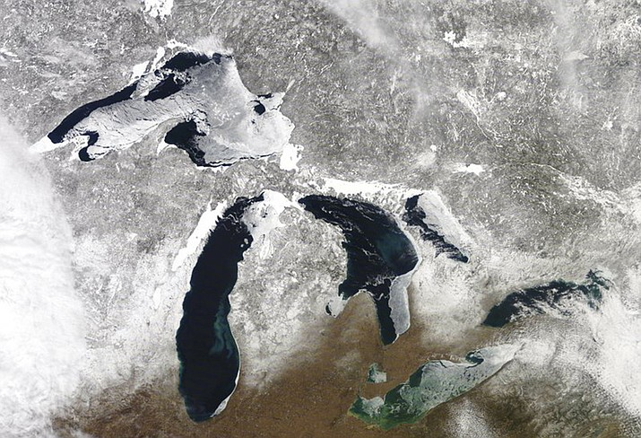In this March 12, 2019 satellite photo provided by NOAA, shows the Great Lakes in various degrees of snow and ice. A scientific report says the Great Lakes region is warming faster than the rest of the U.S., which likely will bring more flooding and other extreme weather events such as heat waves and drought. The warming climate also could mean less overall snowfall even as lake-effect snowstorms get bigger. The report by researchers from universities primarily from the Midwest says agriculture could be hit especially hard, with later spring planting and summer dry spells. (NOAA)