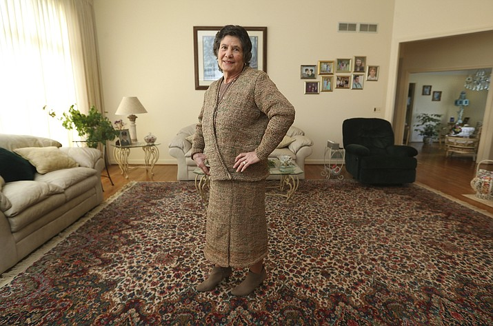 This March 19, 2019 photo shows Rosa Ferrigno wearing a suit that she made from 300 plastic grocery bags in Greece, N.Y. Ferrigno spent two months over the winter knitting a skirt and jacket from filmy brown bags scissored into thin strips tied together to make yarn. She says she did it just for fun.(Jamie Germano/Democrat & Chronicle via AP)