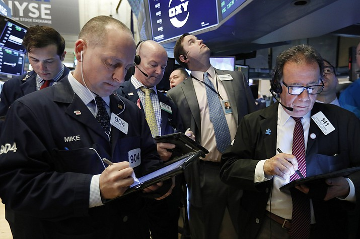 In this March 13, 2019, file photo traders gather at the post that handles Oaktree Capital Group on the floor of the New York Stock Exchange. The U.S. stock market dropped Friday, March 22, on fears of a global economic slowdown. (Richard Drew/AP, File)