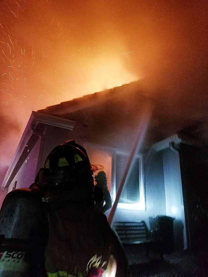 A firefighter battles an early morning March 14 fire that may have started in the garage of a house on the 5000 block of Coriander Court in Pinon Oaks and ultimately moved to the house. (Conrad Jackson, Prescott Fire/Courtesy photo)