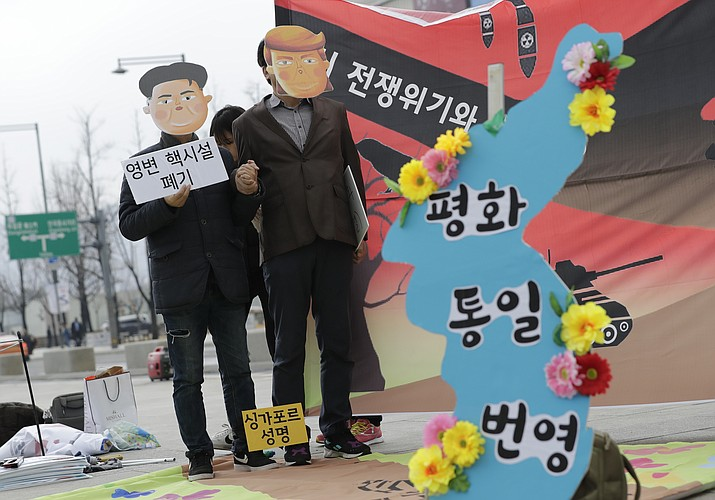Protesters wearing masks of U.S. President Donald Trump and North Korean leader Kim Jong Un stand near the map of Korean Peninsula during a rally demanding the denuclearization of the Korean Peninsula and peace treaty near the U.S. embassy in Seoul, South Korea, Thursday, March 21, 2019. (Lee Jin-man/AP)