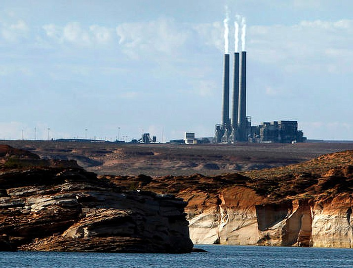 In this Sept. 4, 2011 photo, smoke rises from the stacks of the main plant facility at the Navajo Generating Station, as seen from Lake Powell in Page, Ariz. The Navajo Nation company has ended its pursuit of a coal-fired power plant on the reservation and the mine that feeds it. The decision Friday, March 22, 2019 means the Navajo Generating Station and the Kayenta Mine will close this year, ending decades of operation in northeastern Arizona. The bid by the Navajo Transitional Energy Company had been considered a long-shot. (Ross D. Franklin/AP, File)