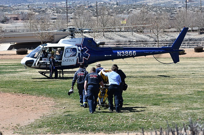 Emergency responders transport a ranch hand to a waiting helicopter in the recreation field at Quailwood Park in Dewey, Arizona on Saturday, March 23, 2019. The 29-year-old man was airlifted to a Phoenix hospital after being thrown from his horse while rounding up cattle at Settler Valley Ranch, located 7.5 miles east of Dewey-Humboldt. (Richard Haddad/WNI)